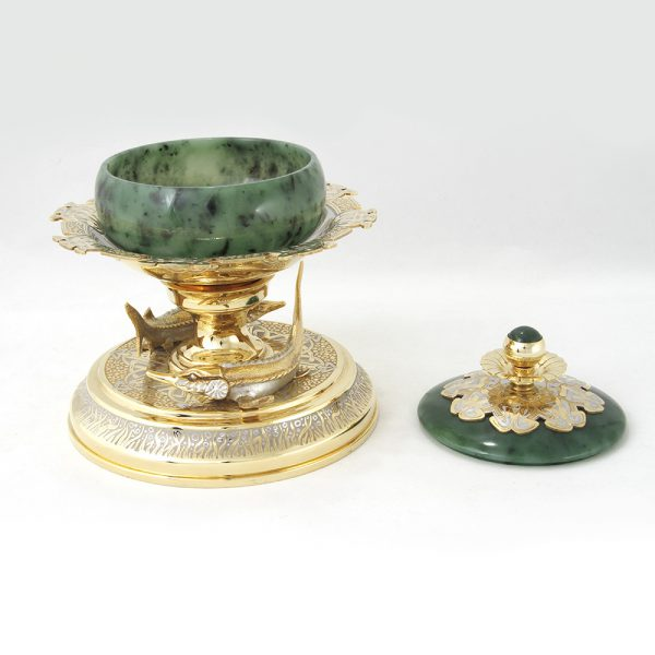 Jade bowl for red and black caviar on a gold platform surrounded by sturgeons
