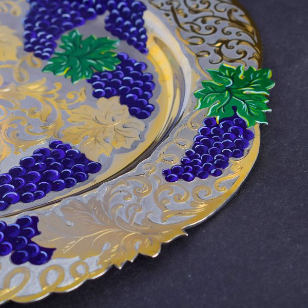 Gold dish with artistic pattern of bunches of grapes