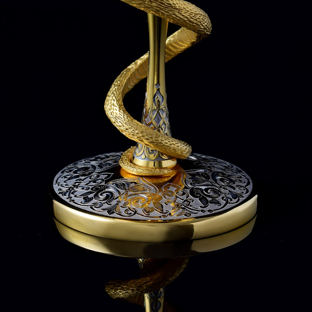 Golden medical cup with a snake