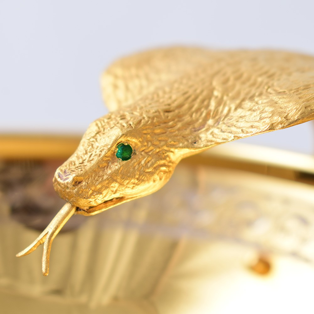 Golden snake head with green stone eyes
