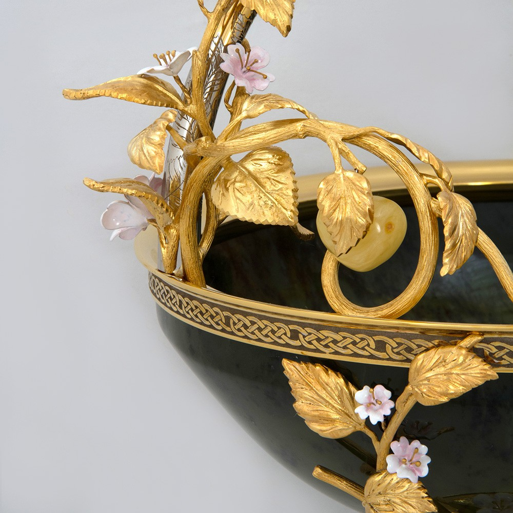 Unusual designer vase with golden leaves and pink flowers.