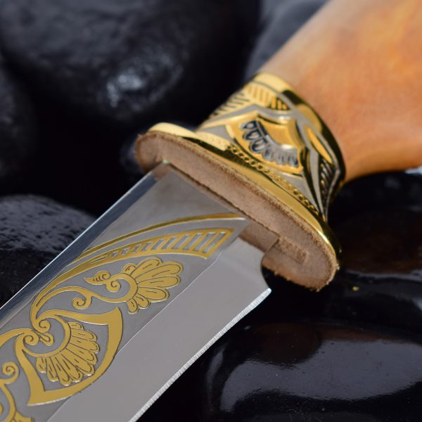 The blade of a knife with a gold pattern
