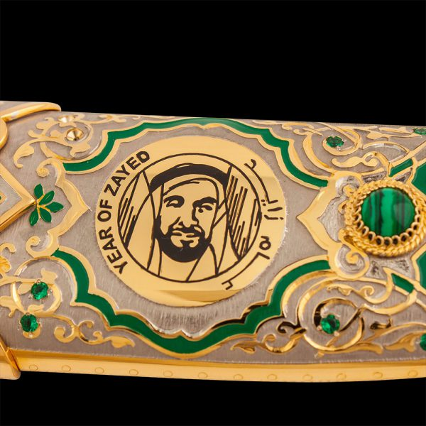 """Gold emblem """"Year of Zayed"""" on a luxurious handmade knives. The scabbard is decorated with green crystals."""