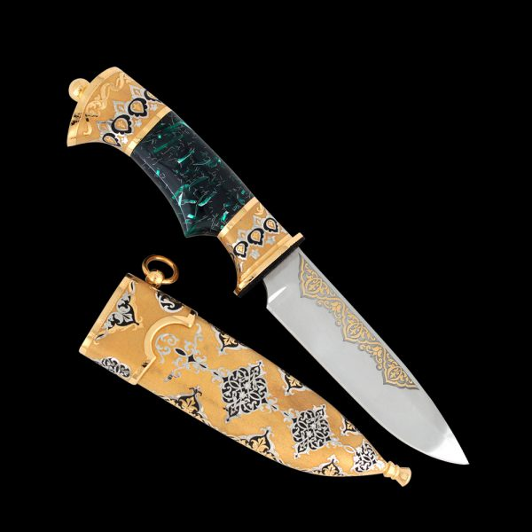 Stylish Arabic knife decorated with metal carvings, gold and a green hilt.