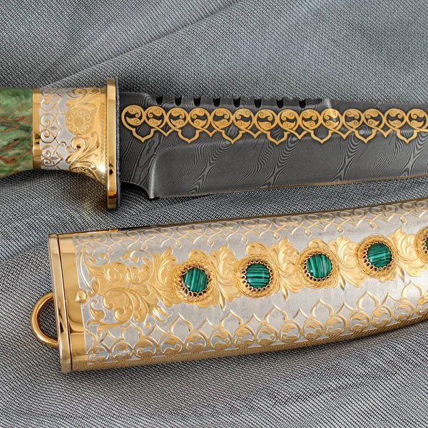 The scabbard is made of metal, its surface is decorated with relief patterns. Such a pattern is formed by manual cutting of metal with a cutter.