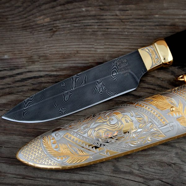 Damascus blade and metal scabbard with engraved eagle pattern.
