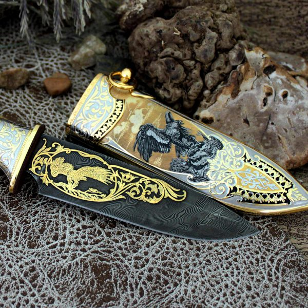 The blade and scabbard of a luxurious knife decorated with a golden image of an eagle