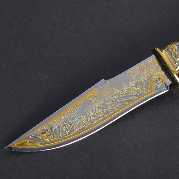 Knife blade made of modern steel with embossed gold pattern on the surface