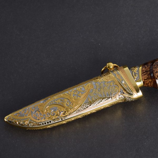 Golden scabbard decorated with floral ornaments in the style of Zlatoust metal engraving.