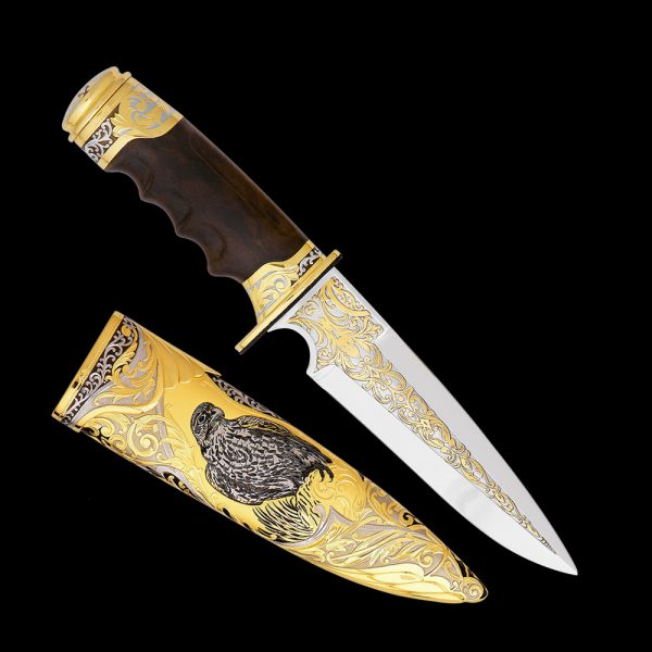 Handmade knife decorated with scabbard. On the sheath is a drawing of a falcon.