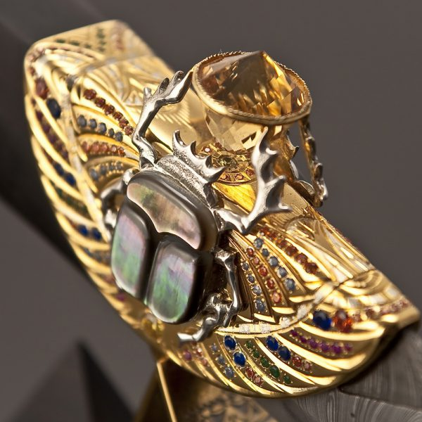In the legs raised to the sky, the scarab holds a light, 96-faced citrine stone with the energy of the sun, purity of thoughts and healing power inside. Its mother-of-pearl wings sparkle in the sun, reflected in the faces of the great Egyptian pyramids.