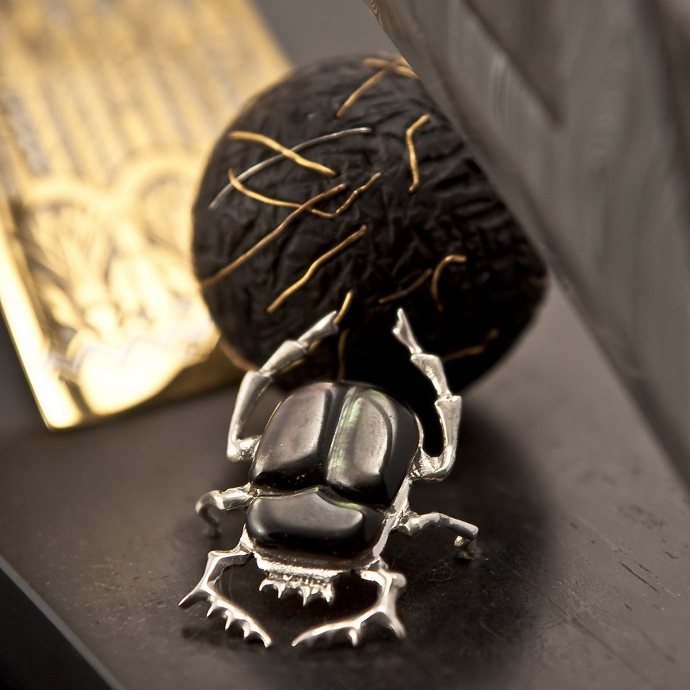 """According to the beliefs of the ancient Egyptians, a scarab rolls its ball with the seeds of life from east to west, like the sun passes through the sky. On the slope of the mountain where the scarab rolls a ball, the """"Ankh"""" sign is depicted – a key of life and a symbol of immortality, b"""