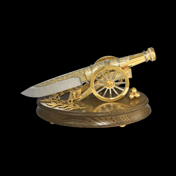 Knife gun - a luxurious exposition of a knife in the form of a golden gun on a wooden base. Exclusive corporate gift.