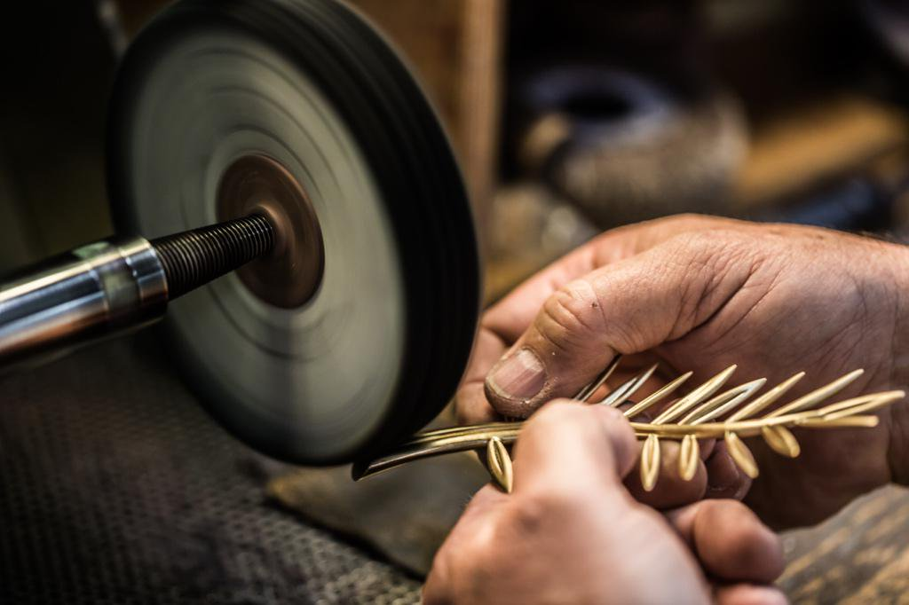 Polishing jewelry parts on an abrasive wheel