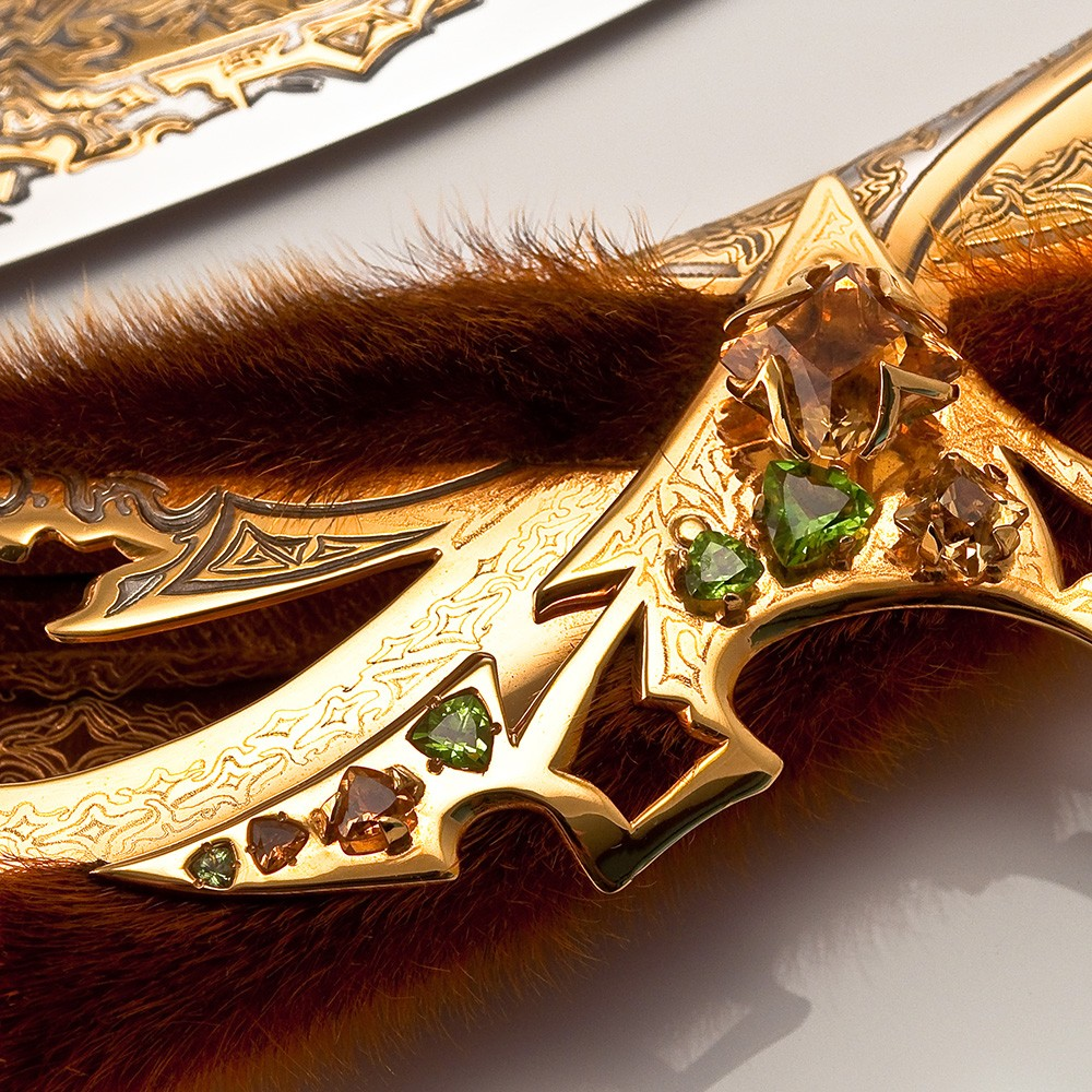 This item is a work of decorative art made in the traditional technique of Zlatoust metal engraving, using galvanic methods of etching, gilding, nickel plating. The dagger also reflected the original combination of jewelry stones and seal fur.