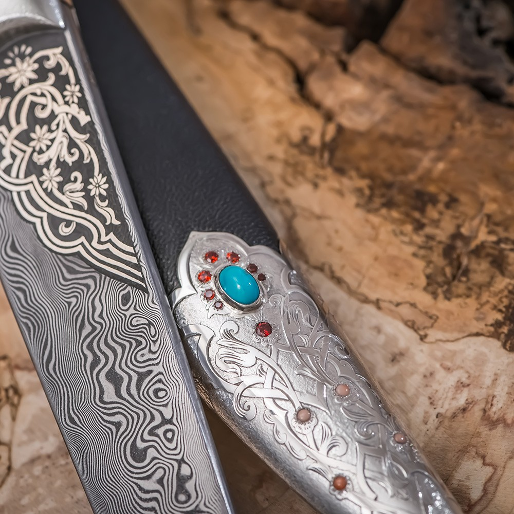 The blade is made of Zladinox damask steel; a floral ornament is applied to a part of the blade using a silver notch.