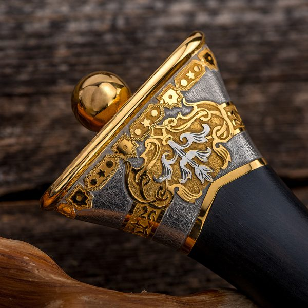 The handle of a dagger expands to the end of its end. The surface of the metal elements is decorated with carvings made by hand with a cutter.