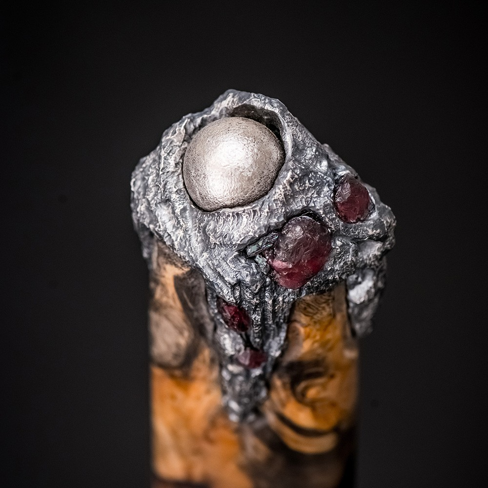 The dagger handle is made of stabilized burl. The handle is decorated with garnets, agates, Martians and a rhodium-plated coating.
