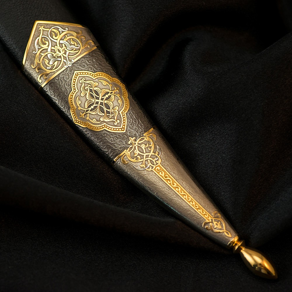 The metal tip of the dagger scabbard with an amazing relief ornament made by an engraving artist manually using a cutter and a microscope.