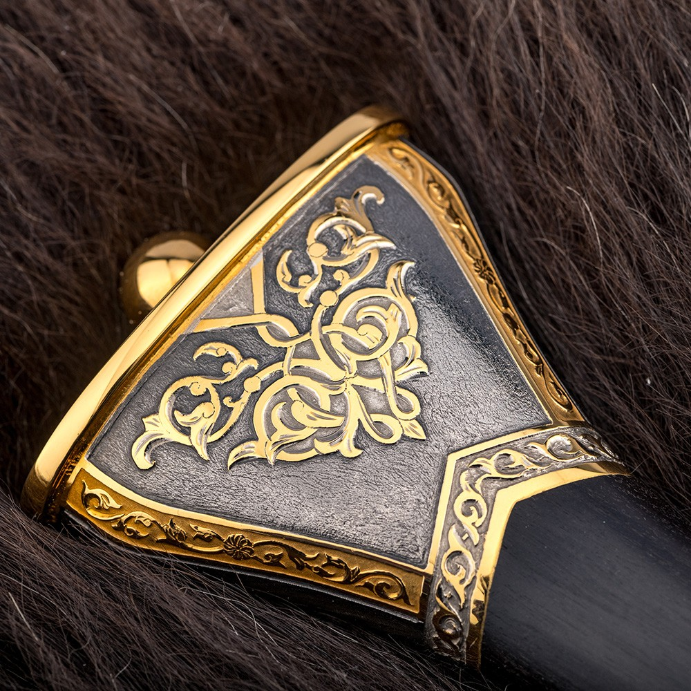 The head of the dagger decorated with hand-carved patterns coated with gold and rhodium