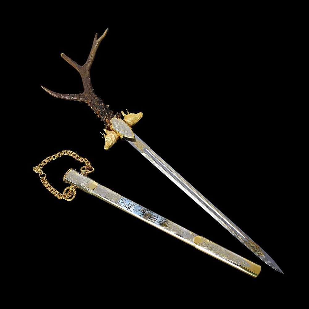 A luxurious dagger with a straight blade adorns the handle of a real roe horn. The guard of the dagger is cast in the form of two roe deer heads covered in gold.