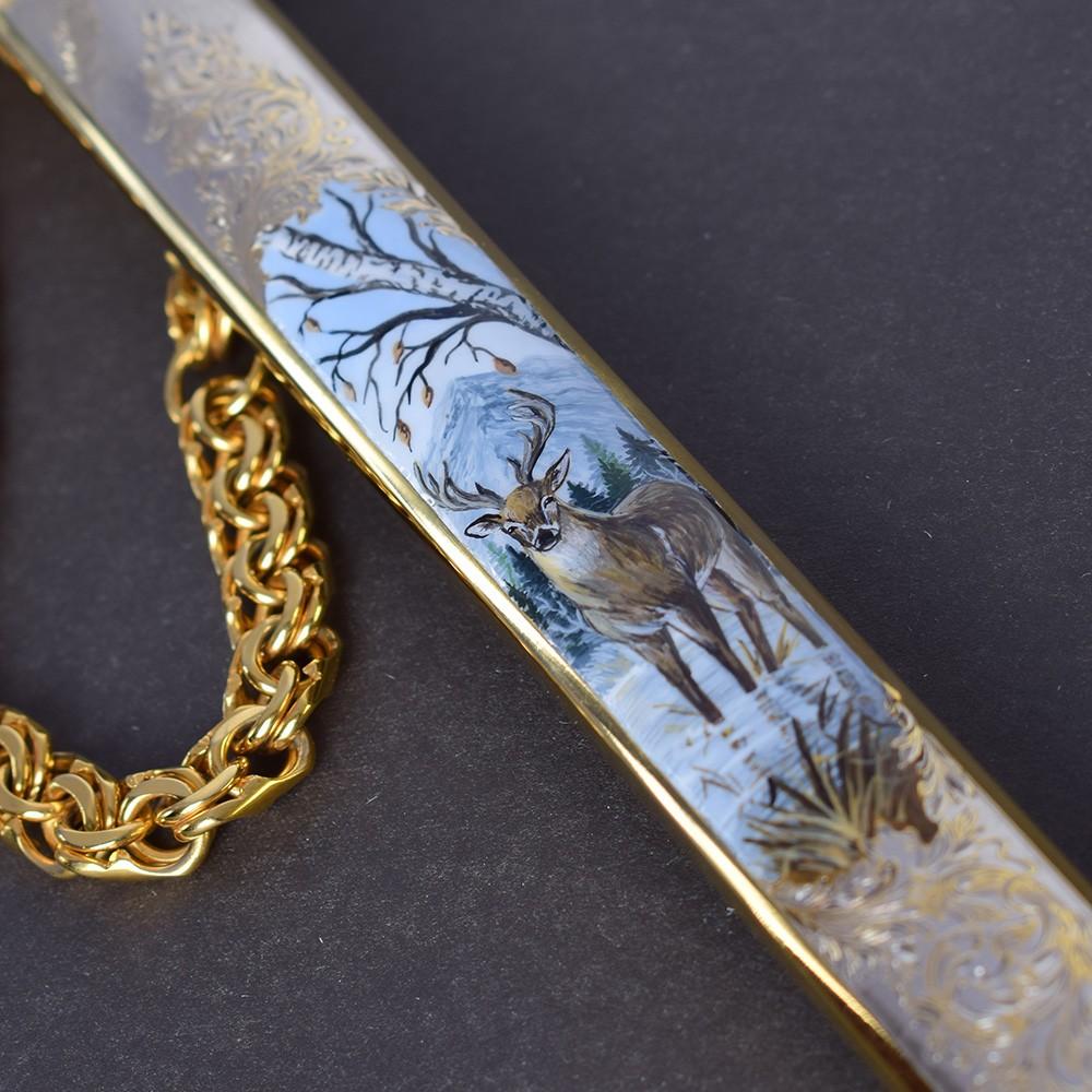 Artistic image of a deer on a metal sheath of a dagger. Handmade souvenir dagger.