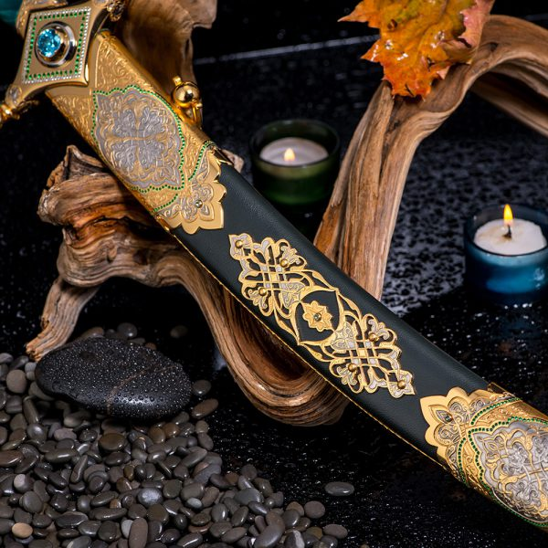 Saber scabbard of the Arabian sword decorated with gold and stones. Gunsmith jewelry