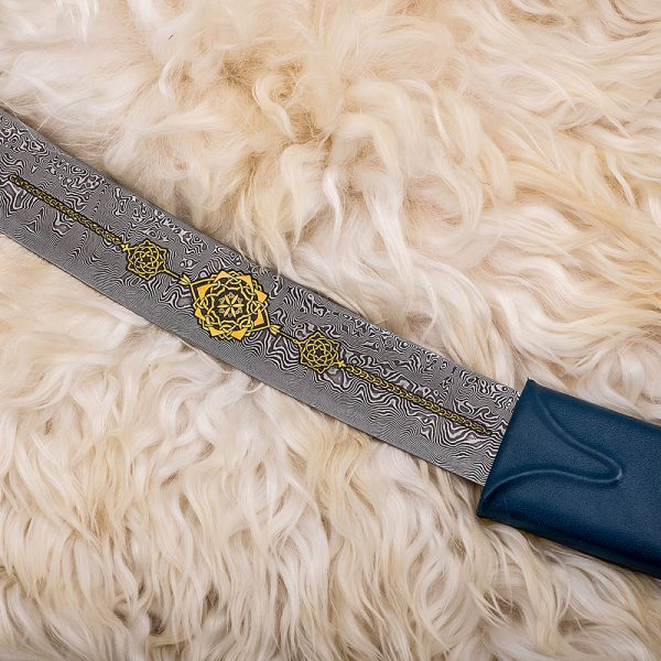 The blade of the Arabian sword with a beautiful damask steel pattern decorated with gold oriental ornaments.