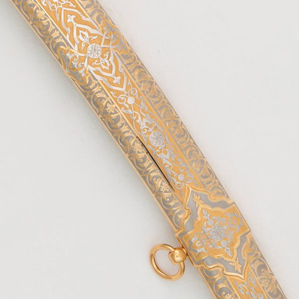 The scabbard of the saber is covered with gold and carved ornament made by the method of engraving on the metal surface.