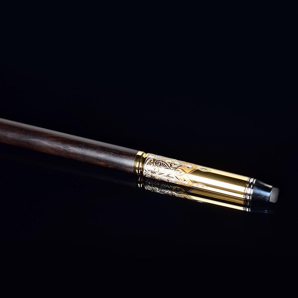 The tip of a cane with a carved pattern.