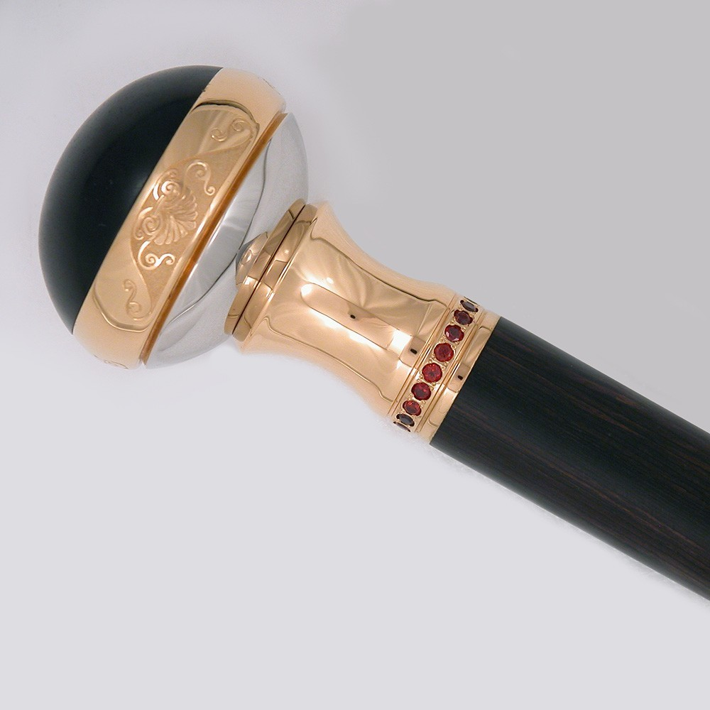 A golden hilt of a handmade cane decorated with red stones and an insert of wood.