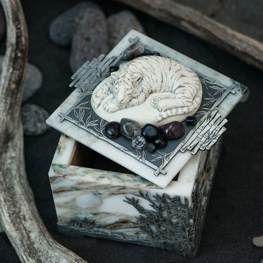 A square box of stone with a tiger on the lid.