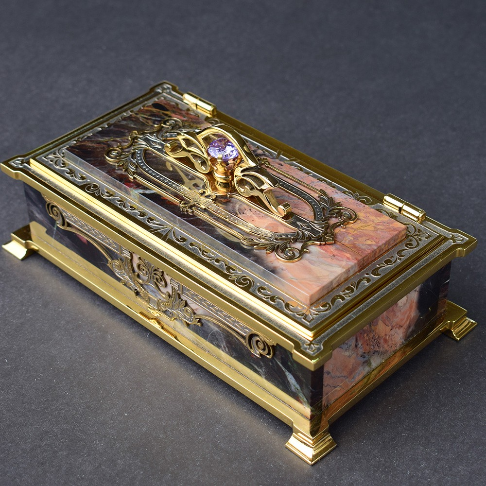 Box for money in a case made of natural stone and a carved rim coated with gold.