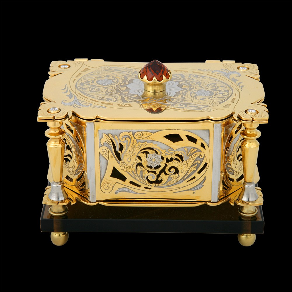 Golden casket - Lady. Decorated with patterns and cut-outs. A large red crystal is mounted on the lid.
