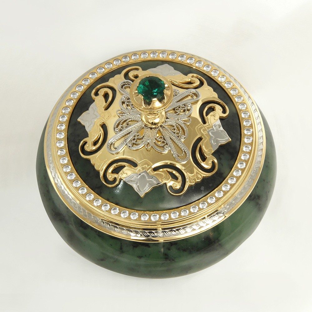 Metal parts of the stone case are made according to the sketch of the designer and plated with nickel and gold. Gold is combined with a rich green shade of natural stone. A large green stone is inlaid in the handle of the casket. The bezel is decorated with a ring of transparent phianites.