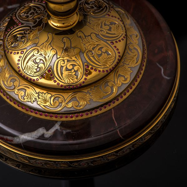 A candle holder made of metal and Ural jasper, decorated in the style of Zlatoust engraving on metal, will give the house a special charm and will testify to a good sense of taste and noble luxury.
