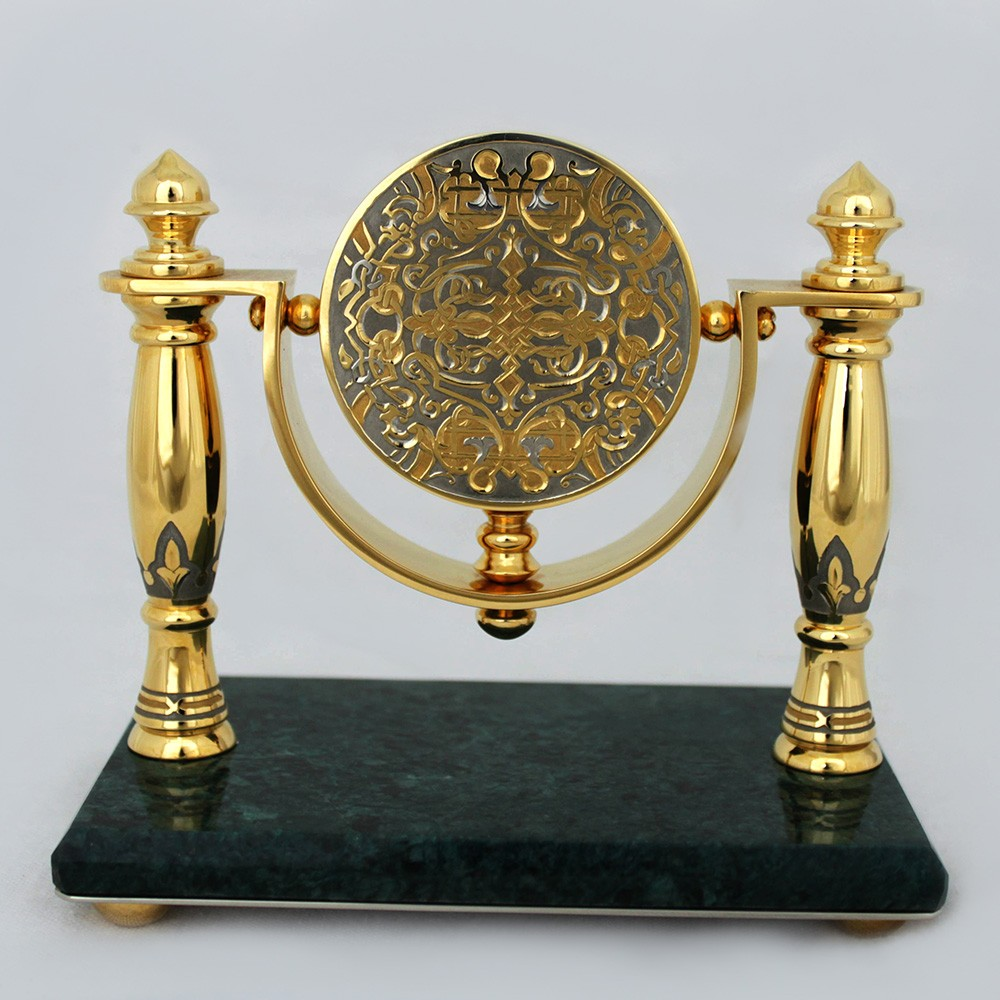A round clock suspended on gold columns