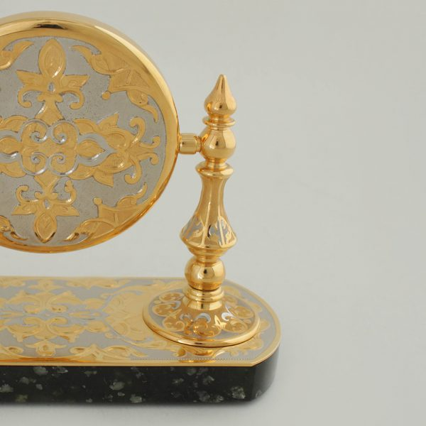 Gold watch case on a stone base