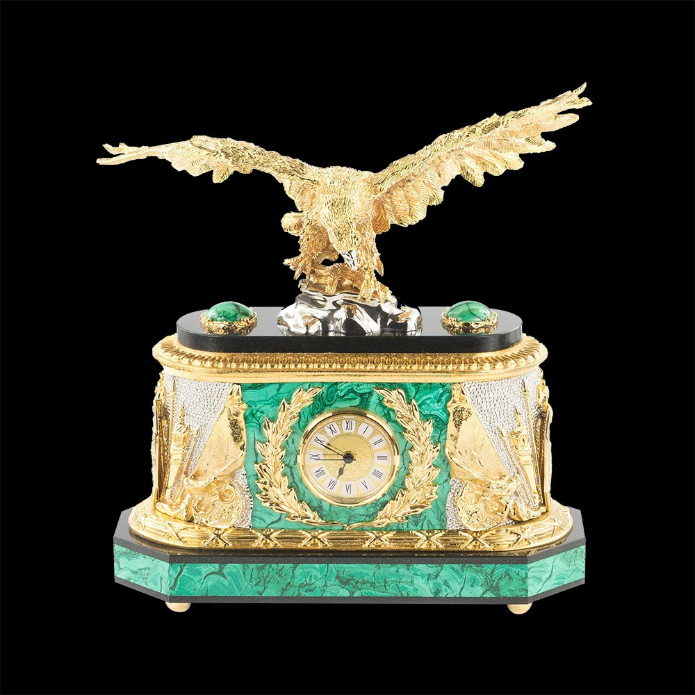 The malachite clock case is equipped with a movement which is presented on the front side with a round dial of small diameter. Roman numerals are depicted on a golden background of the dial, making the exact time easily distinguishable.