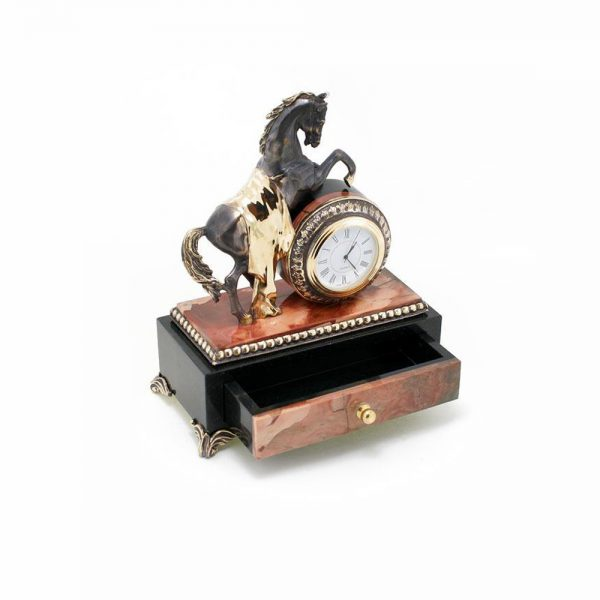 Handmade stone casket with a clock and a steel statuette of a horse.