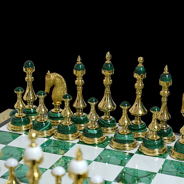 Chess figures from malachite and gold. The figures are located on a board made of snow-white cacholong and green malachite.
