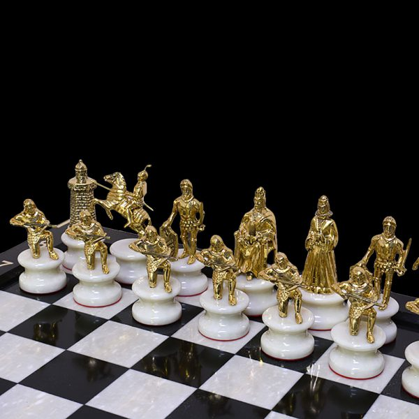 Chess figures of golden knights on a stone pedestal