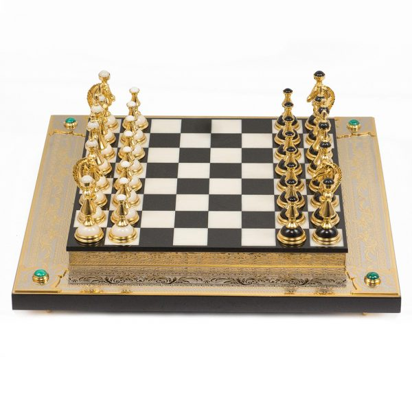 Chess board. Classic handmade chess made of stone and gold. In the corners, chess is decorated with malachite cabochons.