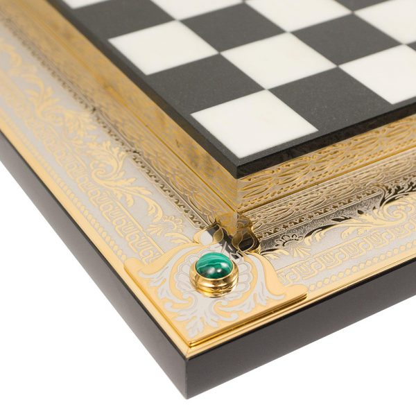 Two-level chessboard made of stone. The contour is decorated with gold plates with embossed engraving