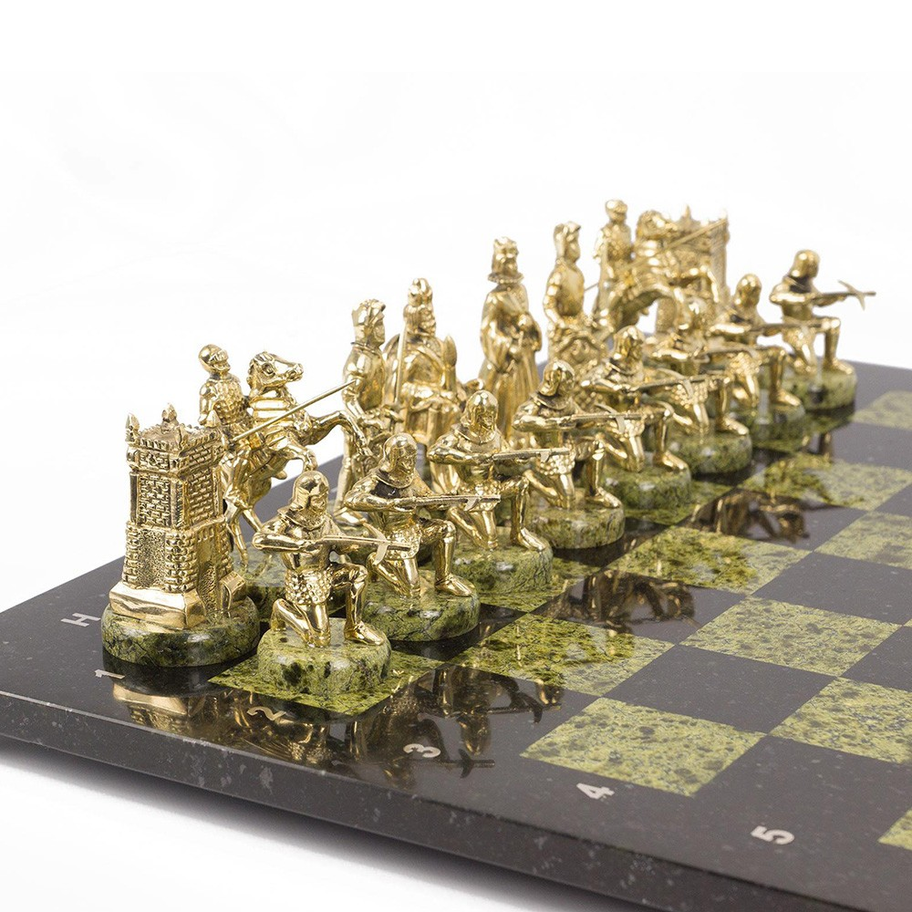Golden chess pieces of medieval warriors. Handwork of the Ural masters.