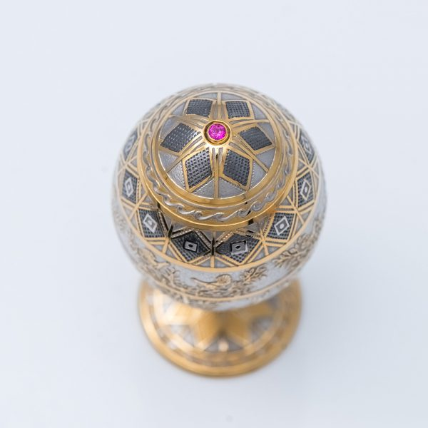 Jewelry egg made of metal covered with gold and ornament.