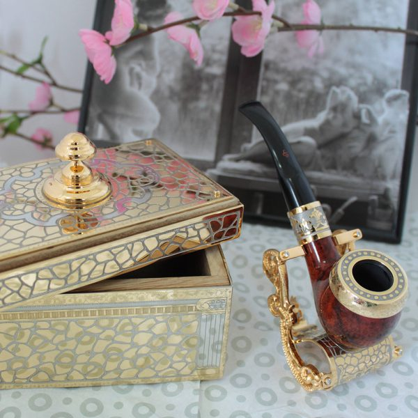 A smoking pipe on a stand and a wooden tobacco box.