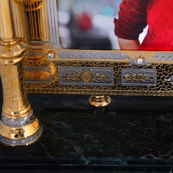 Luxurious photo frame made of metal and gold on the basis of natural stone