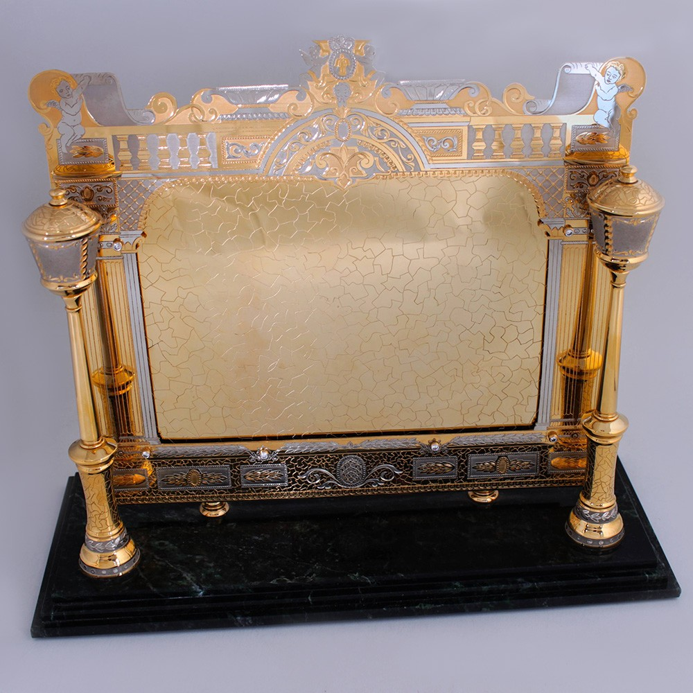 Golden photo frame for interior decoration. Luxurious handwork of jewelers, stone cutters and engravers.