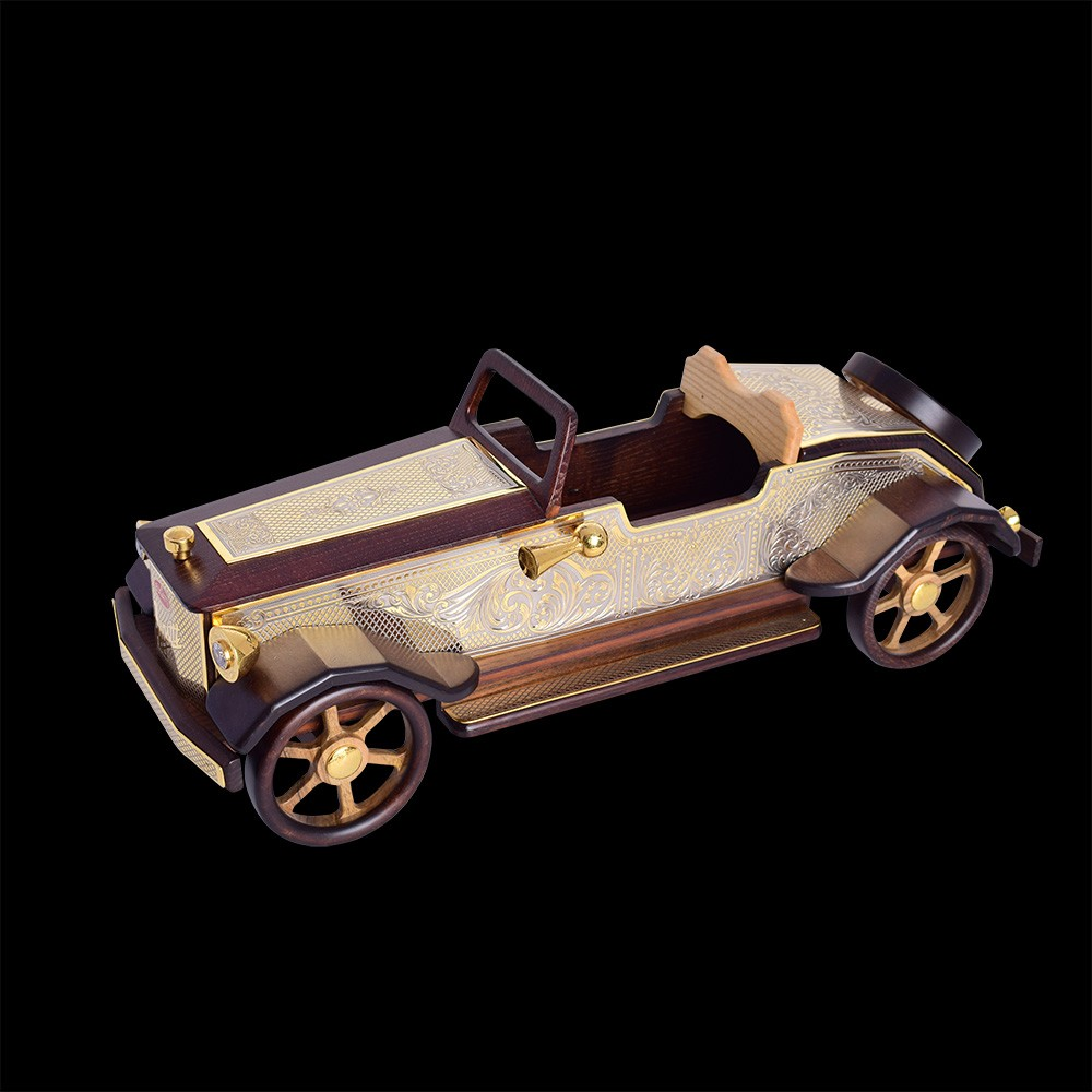 A large model of a retro car carved from wood and decorated with gold lining. Luxury gift to decorate your office